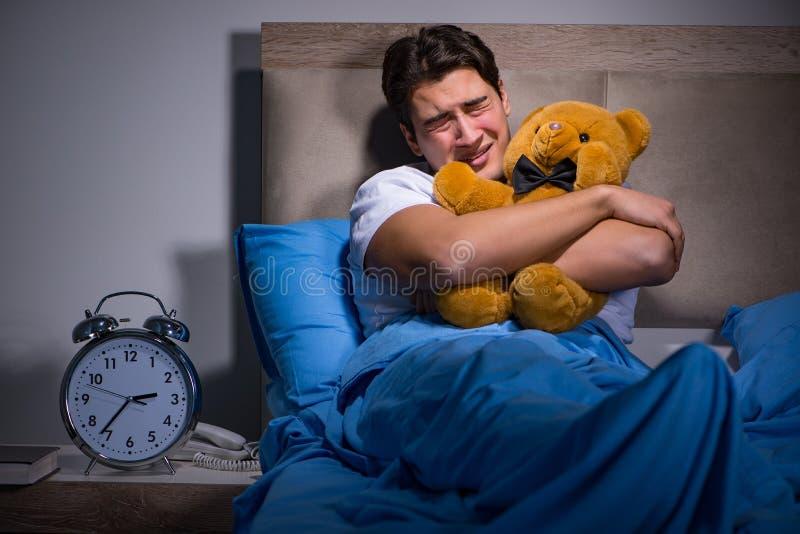 De jonge die man in bed wordt doen schrikken stock afbeeldingen