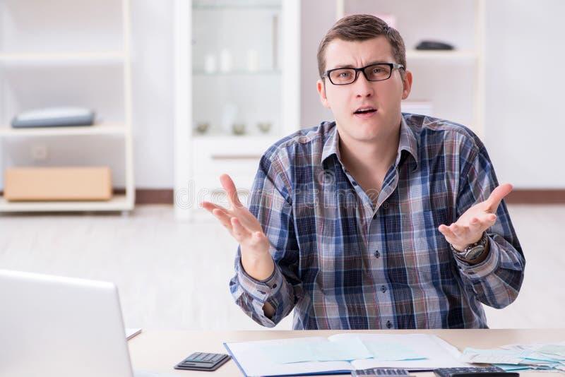 De jonge die man bij zijn huis en belastingsrekeningen wordt gefrustreerd royalty-vrije stock foto