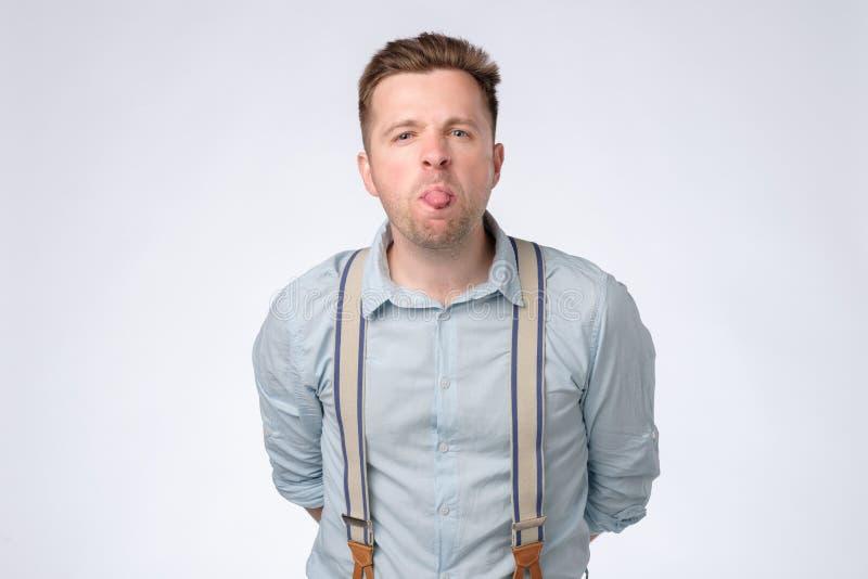 De jonge die mens toont tong, over witte achtergrond wordt geïsoleerd stock foto