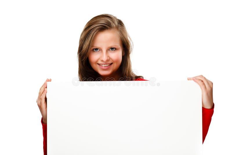 Jonge aantrekkelijke vrouw achter lege raad op witte achtergrond stock fotografie