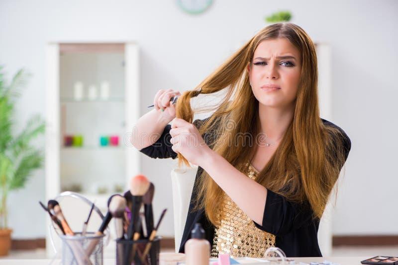 De jonge die vrouw bij haar slordig haar wordt gefrustreerd royalty-vrije stock afbeelding