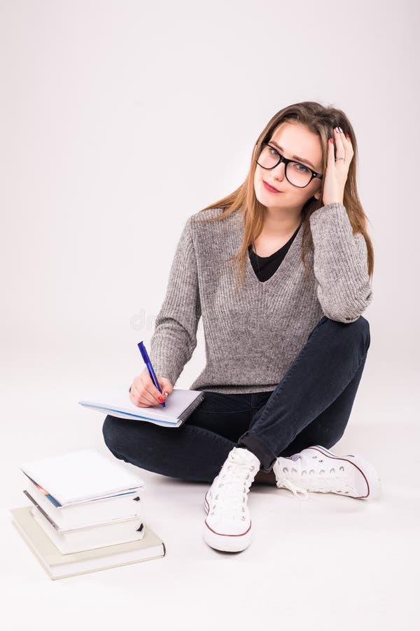 De jonge die zitting van de studentenvrouw op de vloer met boeken wordt omringd, die nota's nemen, die voor examen op Witte achte stock afbeelding