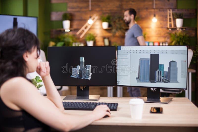 De jonge directeur die van het vrouwenbedrijf aan haar computer werken stock foto's