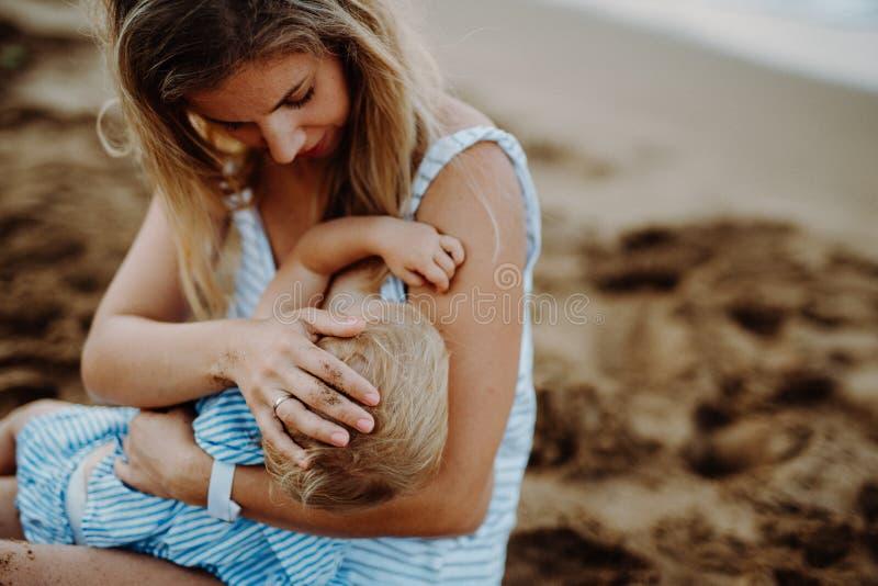 De jonge dochter van de moeder breasfeeding peuter op strand op de zomervakantie stock afbeelding