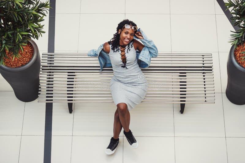 De jonge donker-gevilde vrouw kleedde zich in vrijetijdskleding op de bank in de wandelgalerij stock afbeeldingen