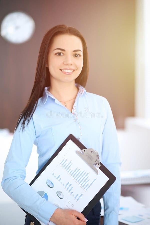 De jonge donkerbruine bedrijfsvrouw kijkt als een studentenmeisje die in bureau werken Spaans of Latijns-Amerikaans meisje gelukk royalty-vrije stock foto's