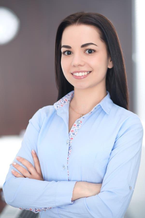 De jonge donkerbruine bedrijfsvrouw kijkt als een studentenmeisje die in bureau werken Spaans of Latijns-Amerikaans meisje gelukk stock foto