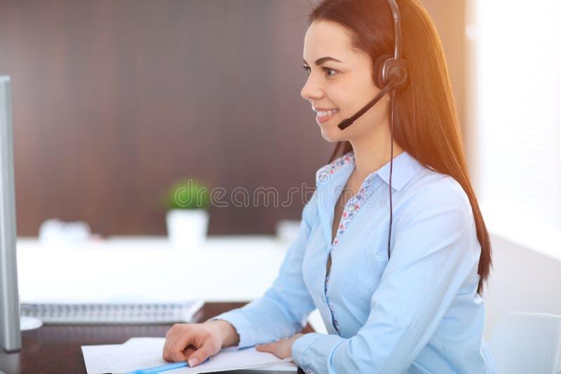 De jonge donkerbruine bedrijfsvrouw kijkt als een studentenmeisje die in bureau werken Spaans of Latijns-Amerikaans meisje die la stock foto's