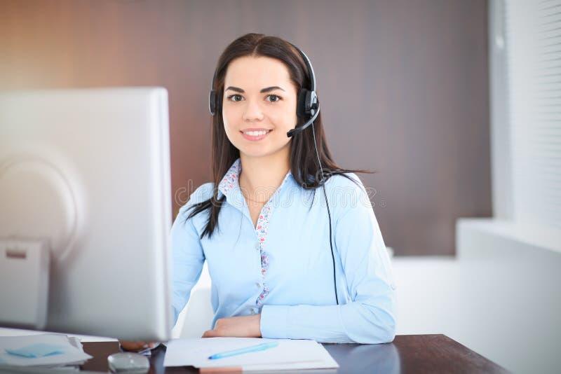 De jonge donkerbruine bedrijfsvrouw kijkt als een studentenmeisje die in bureau werken Spaans of Latijns-Amerikaans meisje die la royalty-vrije stock afbeeldingen