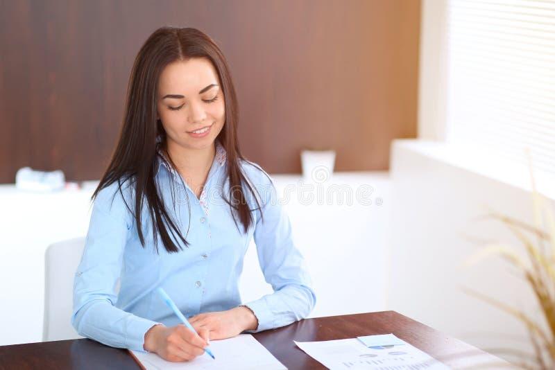 De jonge donkerbruine bedrijfsvrouw kijkt als een studentenmeisje die in bureau werken Spaanse of Latijns-Amerikaanse meisjeszitt stock fotografie