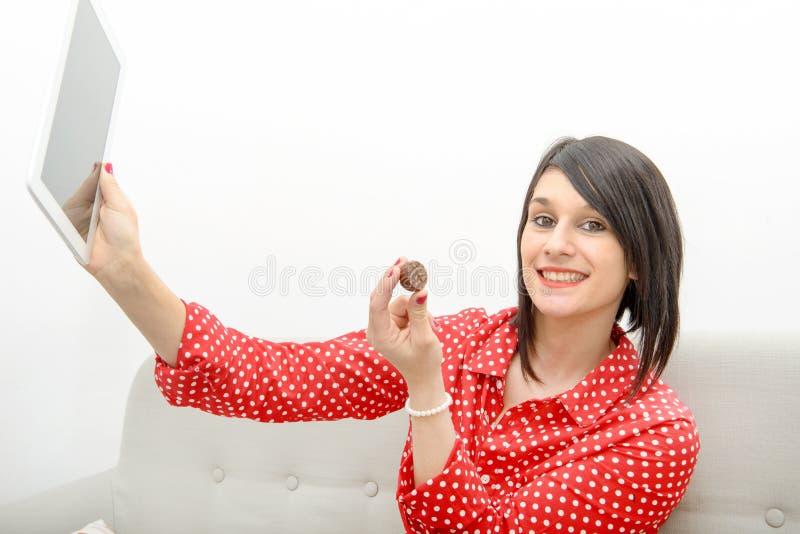 De jonge donkerbruine het glimlachen tablet van de meisjesholding op de bank royalty-vrije stock foto