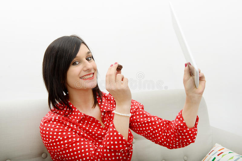 De jonge donkerbruine het glimlachen tablet van de meisjesholding op de bank royalty-vrije stock foto's