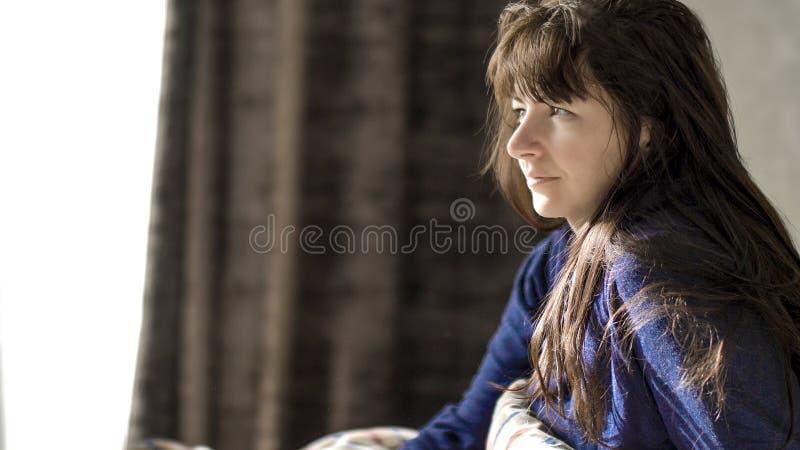 De jonge donkerbruine vrouw glimlacht terwijl het zitten in de ochtend in haar bed stock fotografie