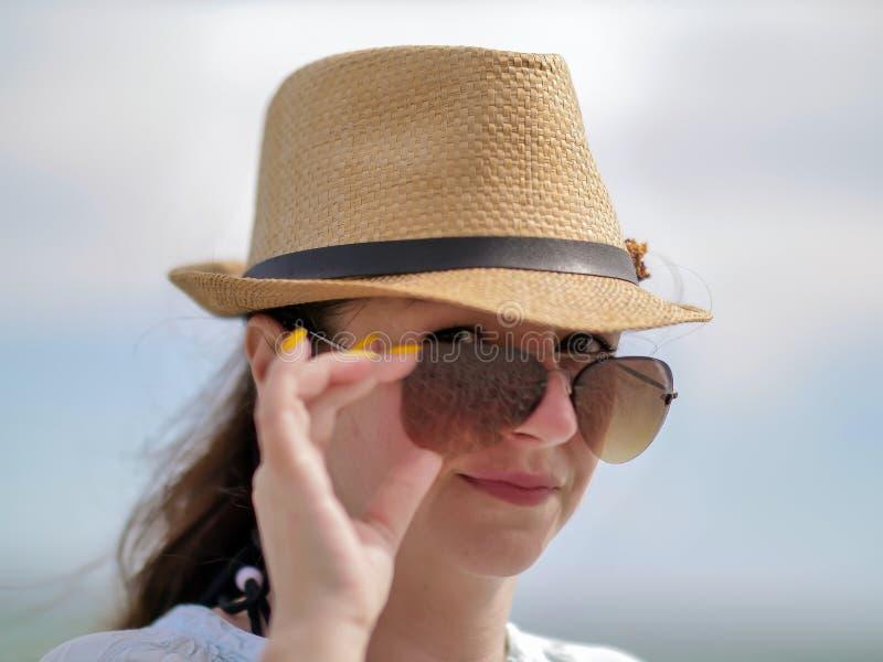 De jonge donkerbruine vrouw maakt zonnebril op haar gezicht, sexy blik recht, onderzoekt de camera royalty-vrije stock foto's