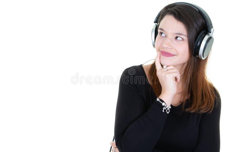 De jonge donkerbruine vrouw met hoofdtelefoons kijkt linker kopieert omhoog opzij ruimte stock foto