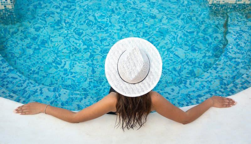 De jonge donkerbruine vrouw met lang haar in hoed, in zwempak is aanwezig stock afbeeldingen