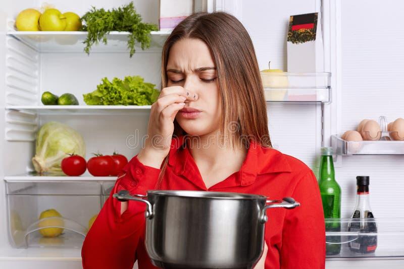 De jonge donkerbruine vrouw met ontstemde uitdrukking ruikt bedorven soep in hutspotpan, voelt thuis muffe geurkeuken, bevindt zi stock afbeeldingen