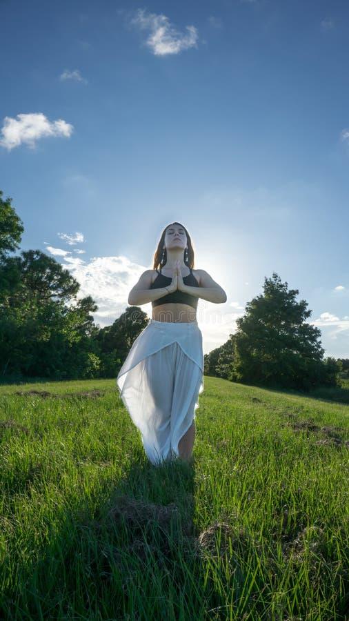 De jonge donkerbruine vrouw in namaste stelt het bidden en dankbaar in aard met zonlicht het verlichten van de rug stock foto's