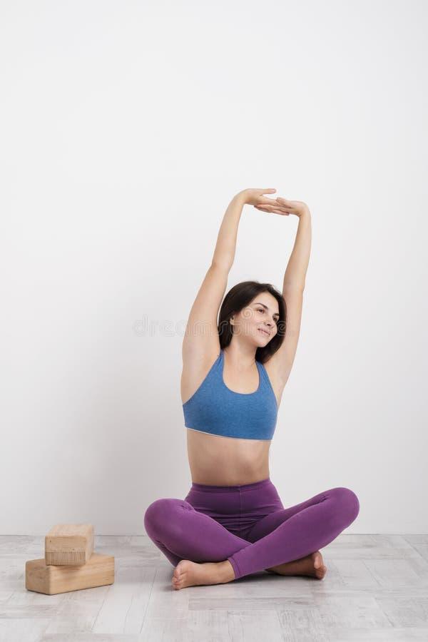 De jonge donkerbruine vrouw in purpere beenkappen en een sportent-shirt doet oefeningen op de vloer Saldi op de blokken en royalty-vrije stock foto's