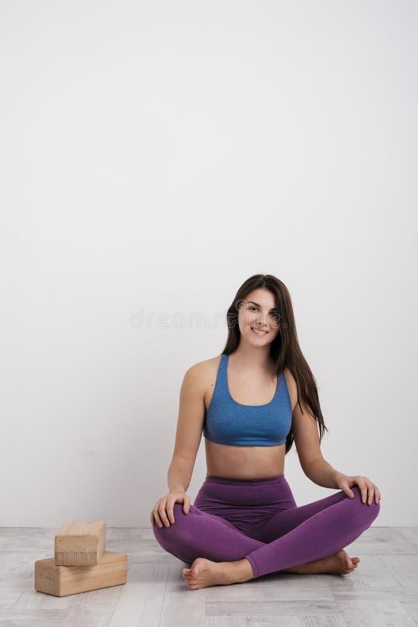 De jonge donkerbruine vrouw in purpere beenkappen en een sportent-shirt doet oefeningen op de vloer Saldi op de blokken en royalty-vrije stock fotografie