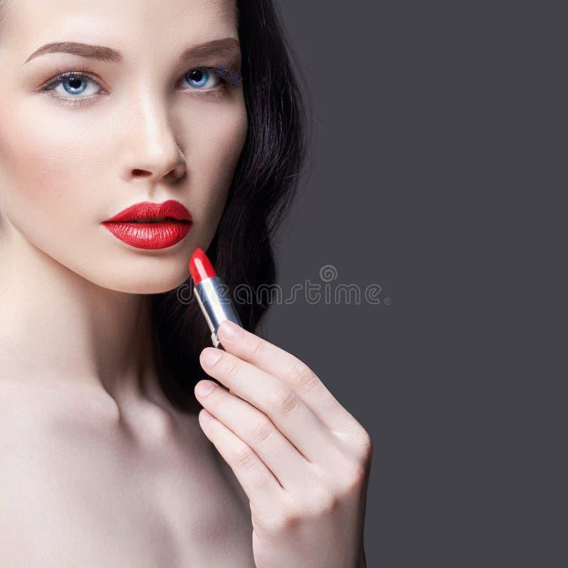 De jonge donkerbruine vrouw schildert haar lippen heldere rode lippenstift Heldere avondmake-up Naakt meisje die haar gezicht en  royalty-vrije stock afbeelding