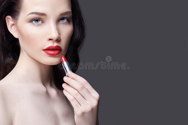 De jonge donkerbruine vrouw schildert haar lippen heldere rode lippenstift Heldere avondmake-up Naakt meisje die haar gezicht en  royalty-vrije stock fotografie