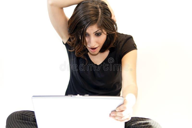 De jonge Donkerbruine Vrouw vindt Verrassing op Computer stock foto
