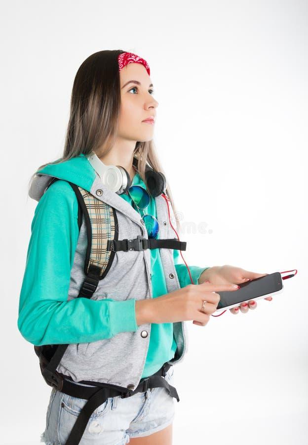 De jonge donkerbruine vrouwelijke student status, onderzoekt de afstand en het houden van uw smartphone royalty-vrije stock afbeeldingen