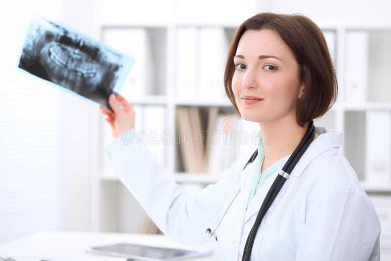 De jonge donkerbruine vrouwelijke tandartszitting bij de lijst en onderzoekt tandröntgenstraal stock fotografie