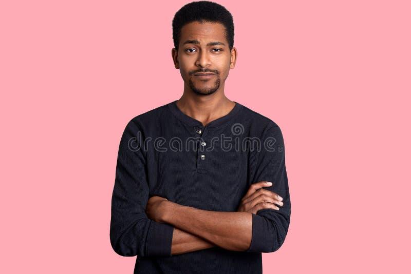 De jonge donkere gevilde mens met kalme uitdrukking, korte kapsel en baard, kleedt toevallig overhemd en houdt handen gekruist Zw stock afbeeldingen