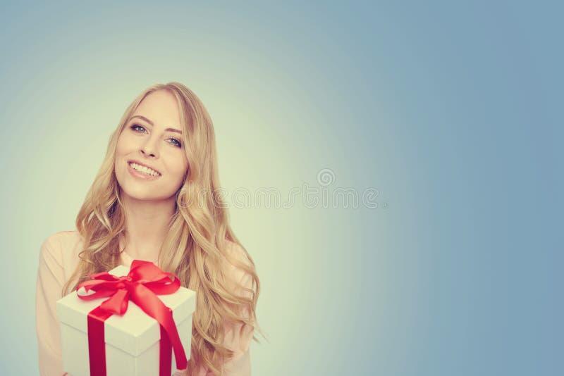 De jonge doos van de de greepgift van de vrouwen gelukkige glimlach in handen stock foto