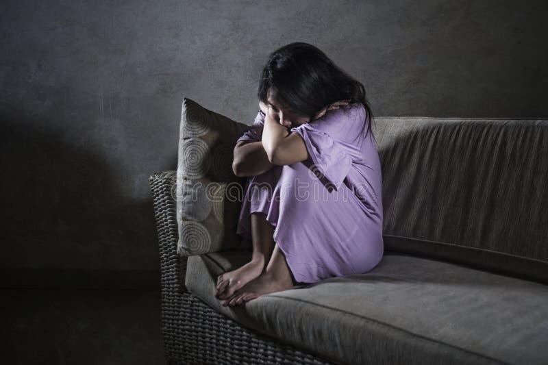 De jonge droevige en gedeprimeerde Aziatische Koreaanse laag die van de vrouwen thuis bank wanhopige en hulpeloze lijdende bezorg royalty-vrije stock afbeelding