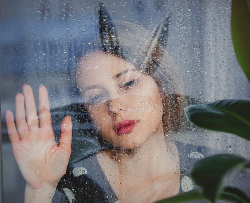 De jonge droevige vrouw dichtbij nat venster na de regen mist de ficusinstallatie stock foto's