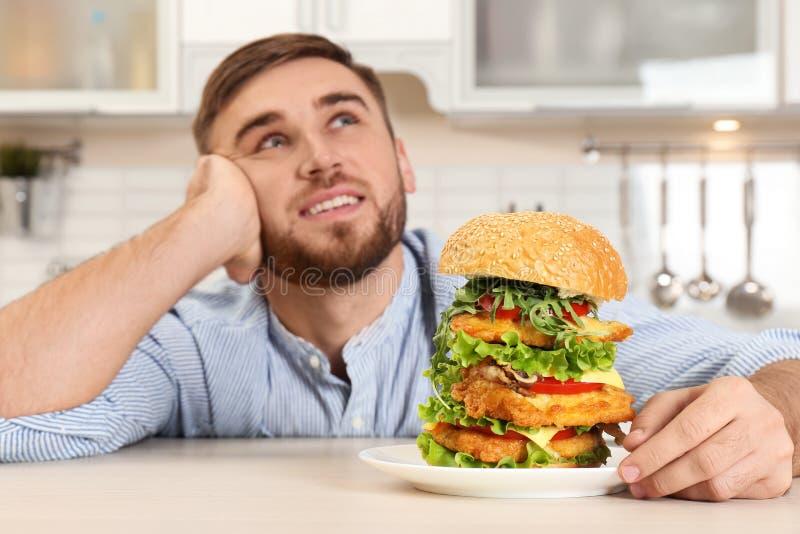 De jonge dromerige plaat van de mensenholding met reusachtige hamburger stock afbeelding