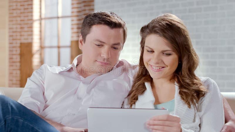 De jonge echtgenoot en de vrouw die weekend zoeken reizen samen op tablet, online boekend stock foto