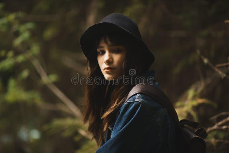 De jonge eenzame zitting van het toeristen cutie meisje op steen op kust van rivier in bergen in wild terrein en het tevredenstel stock foto