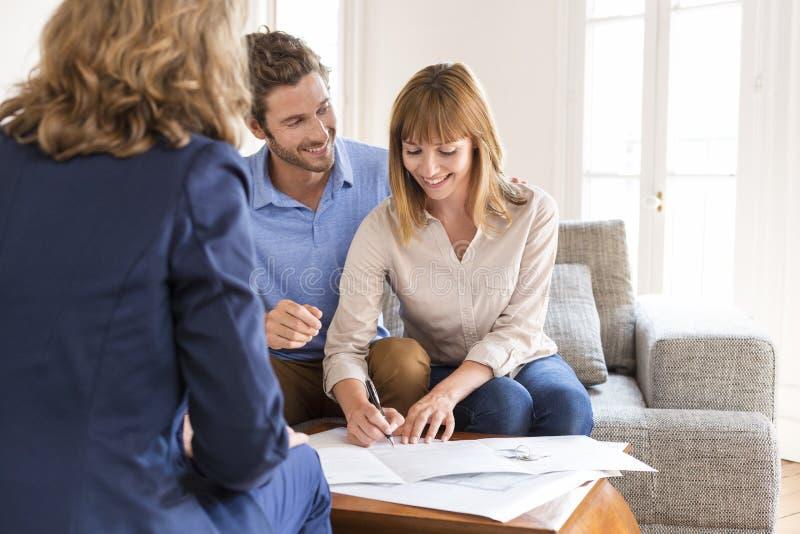 De jonge eigenaars koppelen het ondertekenen van een contract voor huisinvestering royalty-vrije stock afbeelding
