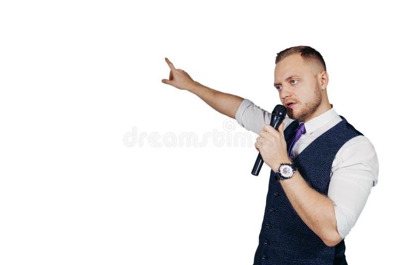 De jonge elegante sprekende microfoon die van de mensenholding met het richten van vinger spreken Geïsoleerdj op witte achtergron royalty-vrije stock foto
