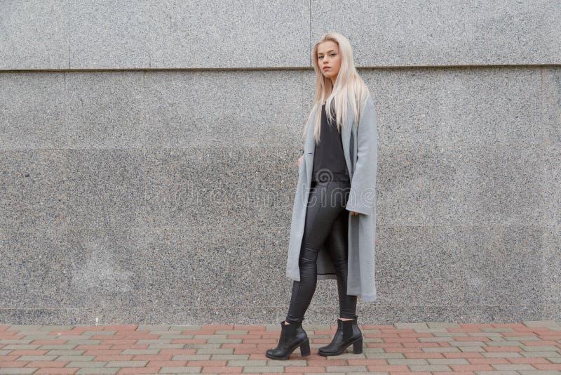 De jonge elegante vrouw die van de manierstijl in grijze bontjas bij stadsstraat lopen stock afbeeldingen