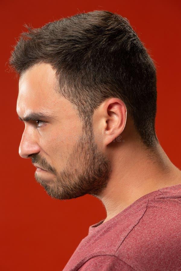 De jonge emotionele boze man die op rode studioachtergrond gillen stock foto's