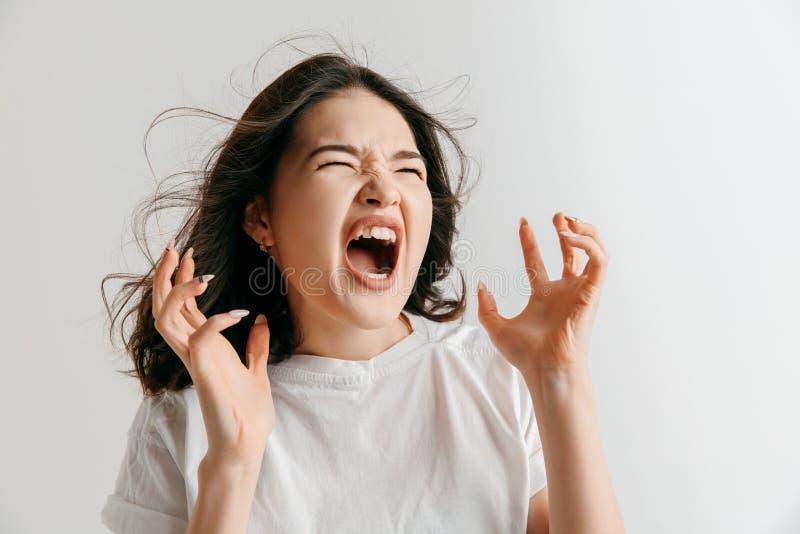 De jonge emotionele boze vrouw die op grijze studioachtergrond gillen royalty-vrije stock afbeelding