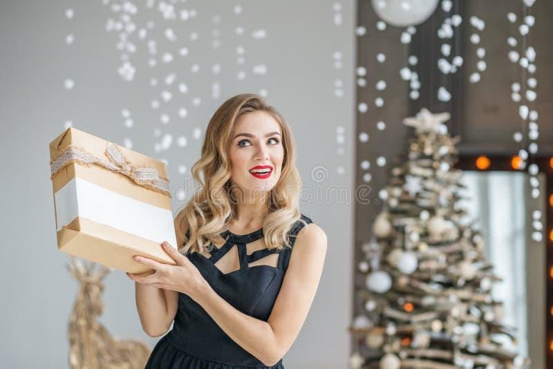 De jonge emotionele vrouw houdt een heden en glimlacht Concept Gelukkig Kerstmis en Nieuwjaar, de winter, partij stock foto's