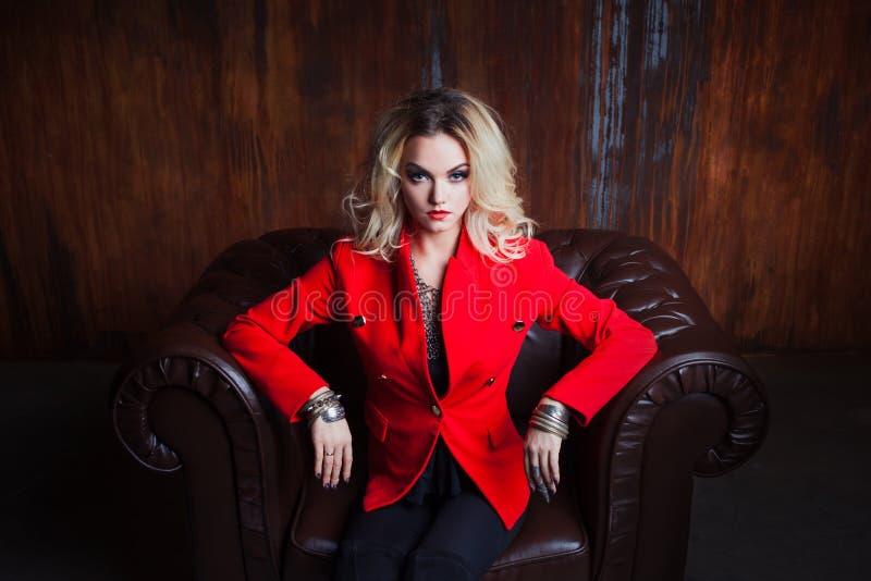 De jonge en aantrekkelijke blonde vrouw in rood jasje zit in leerleunstoel, grunge roestige muur als achtergrond stock foto's