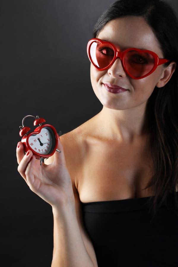De jonge en mooie vrouw met hart gaf glazen en hart-vorm alarm clocker op zwarte achtergrond gestalte royalty-vrije stock foto's