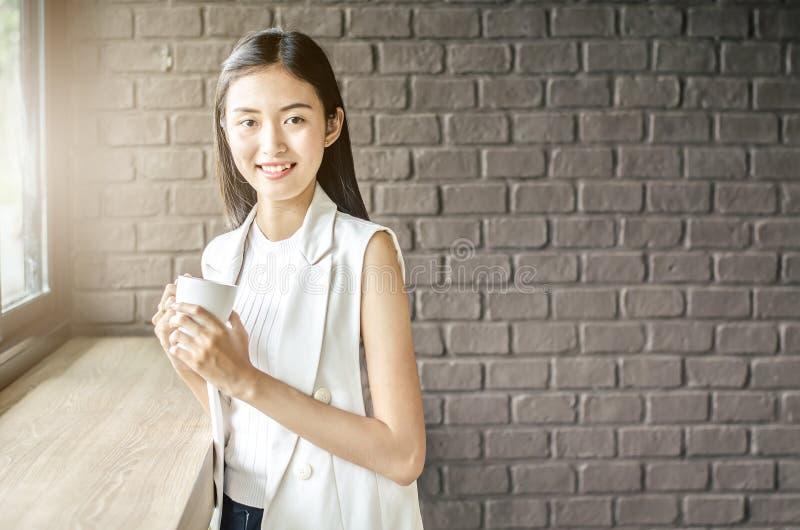 De jonge en mooie vrouw van Azië met kop van koffieglimlach in koffie royalty-vrije stock foto