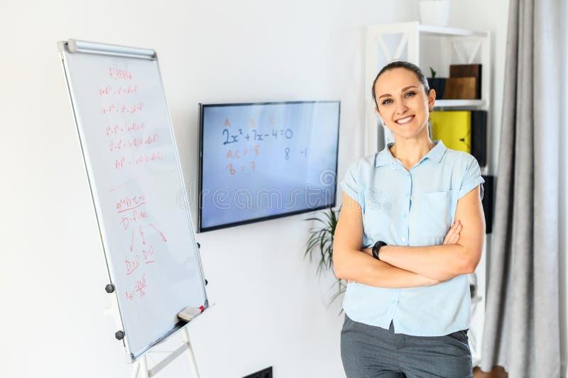 De jonge en zelfverzekerde vrouwelijke leraar, de leerling gebruikt een tikdiagram en monitor voor klassen royalty-vrije stock foto