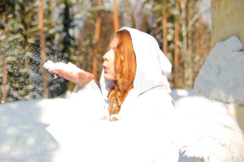 de jonge engel die van blondekerstmis op de sneeuwvlokken blazen stock afbeelding