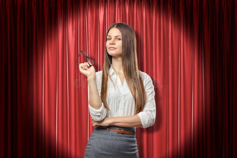 De jonge ernstige donkerbruine glazen van de bedrijfsvrouwenholding in haar hand op de rode achtergrond van stadiumgordijnen royalty-vrije stock fotografie