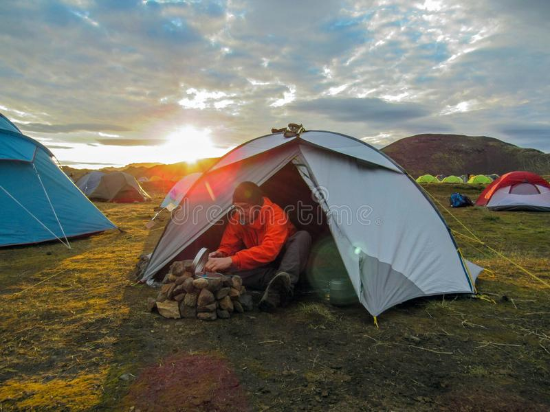 De jonge ervaren wandelaar actieve mens kookt in openlucht diner naast de tent in een wild aardkampeerterrein bij zonsondergang royalty-vrije stock foto's