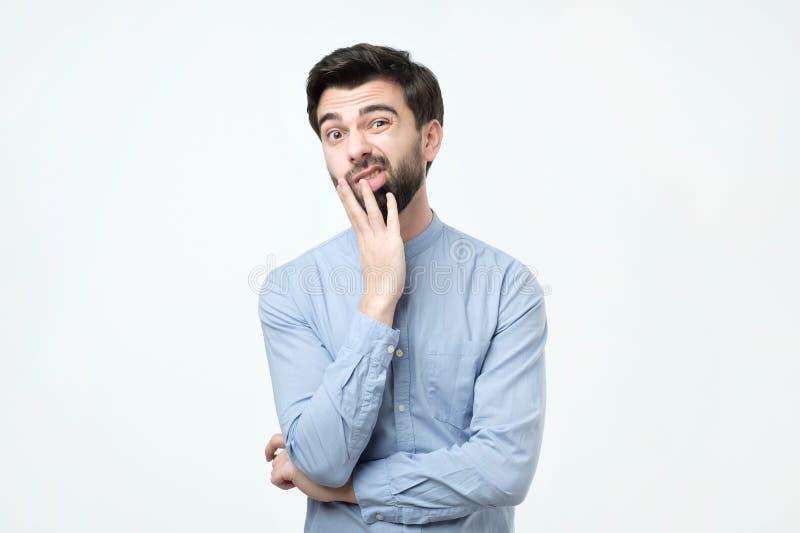 De jonge Europese mens in blauw overhemd denkt incredulously, kijkt door royalty-vrije stock foto's